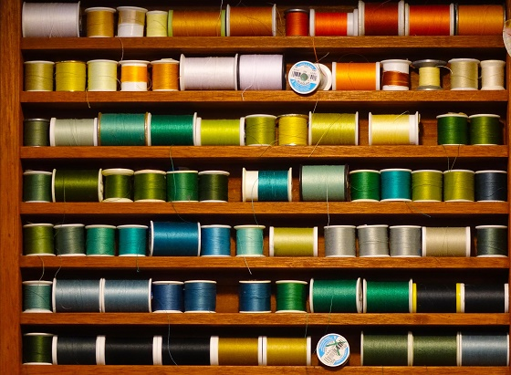 A shelf of different coloured threads